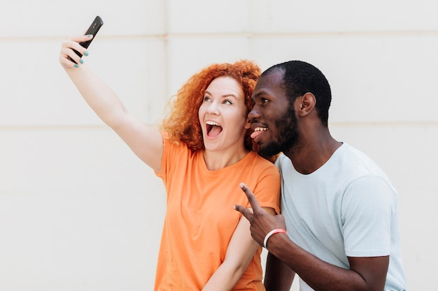 Tiro médio, de, par interracial, levando, um, selfie