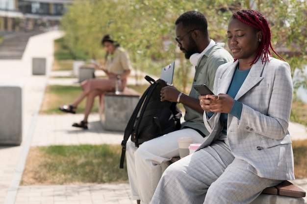 Tiro médio de pessoas sentadas no banco