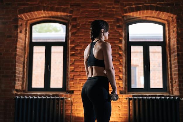 Tiro médio de retrovisor de uma jovem mulher atlética com belo corpo forte, vestindo roupas esportivas segurando halteres durante o treinamento de treino. treino feminino de fitness caucasiano fora exercitando-se no ginásio escuro.