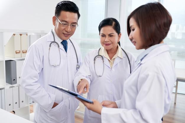 Tiro médio de três médicos analisando lista de sintomas