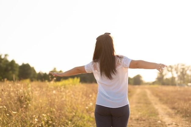 Tiro médio de uma jovem mulher segurando os braços no ar
