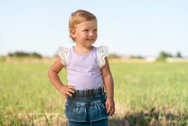 Tiro médio de uma menina sorrindo e olhando para longe