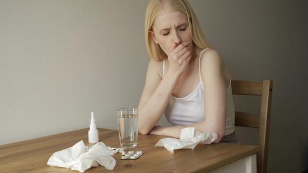 Tiro médio de uma mulher loira com dor de garganta, sentada à mesa da cozinha e tossindo.