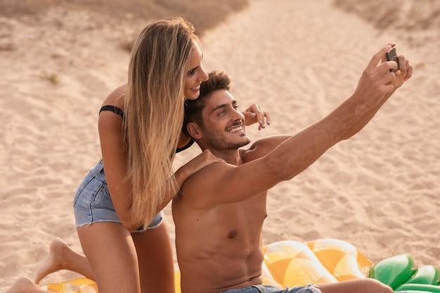 Tiro médio do casal tirando foto juntos