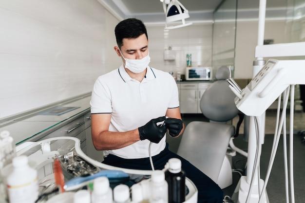 Tiro médio do dentista que verifica o equipamento cirúrgico