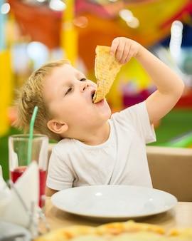 Tiro médio do garoto comendo pizza