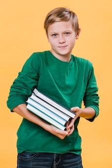 Tiro médio do garoto segurando livros