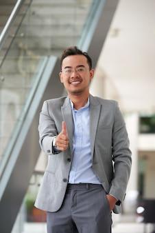 Tiro médio do homem asiático dando um polegar para cima gesto para a câmera