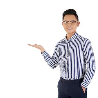 Tiro médio do homem asiático, gesticulando como se estivesse apresentando um produto