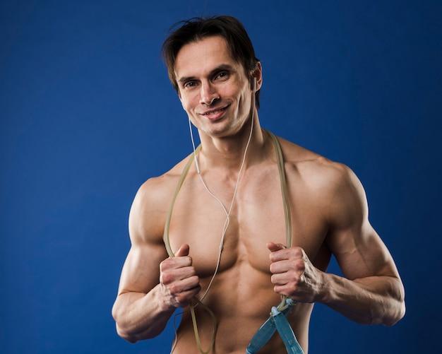 Tiro médio do homem atlético sem camisa sorridente com fones de ouvido