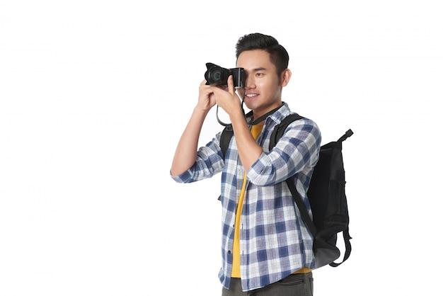 Tiro médio do homem com mochila, tirando uma foto com sua câmera profissional