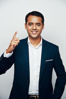 Tiro médio do homem indiano bonito em trajes formais posando contra a parede branca com o ponteiro para cima