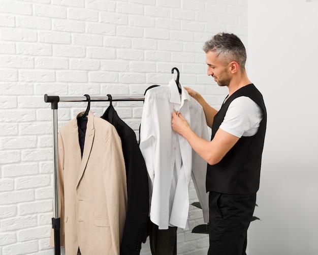 Tiro médio do homem organizando suas camisas