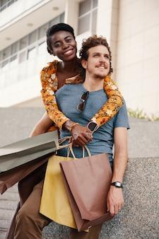 Tiro médio do jovem casal intercultural com sacos de compras, posando para uma foto ao ar livre