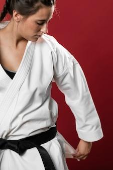 Tiro médio do lutador mulher consertando seu quimono