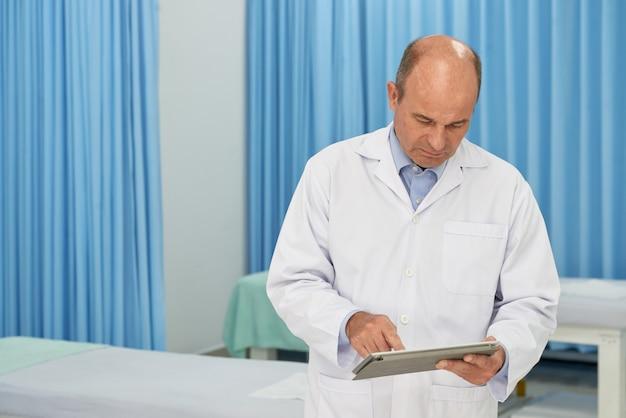 Tiro médio do médico, verificando o histórico médico no dispositivo de almofada digital