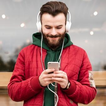 Tiro médio do smiley com fones de ouvido olhando para smartphone