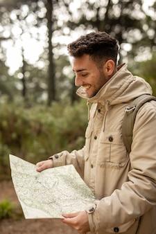 Tiro médio do smiley homem segurando o mapa