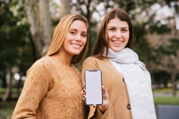 Tiro médio, duas mulheres elegantes, segurando, telefone, em, mãos