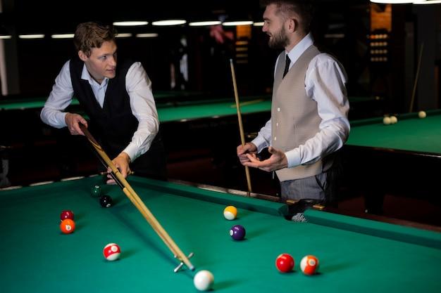 Tiro médio elegante caras jogando bilhar