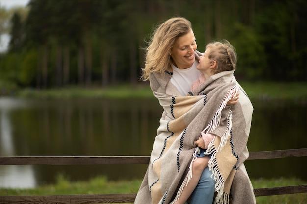 Tiro médio feliz mãe e filho com cobertor