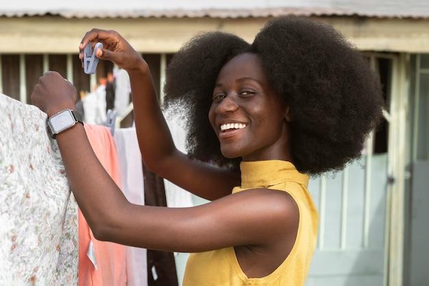 Tiro médio feminino pendurando roupas para secar