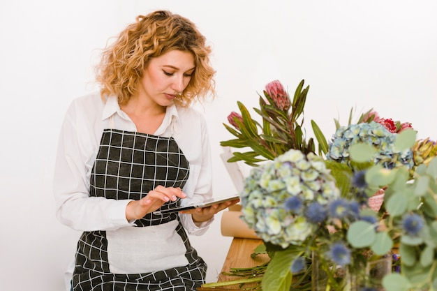 Tiro médio florista digitando algo sobre tablet