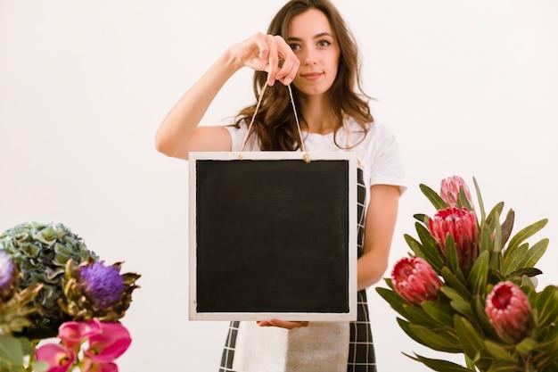 Tiro médio florista segurando uma placa preta