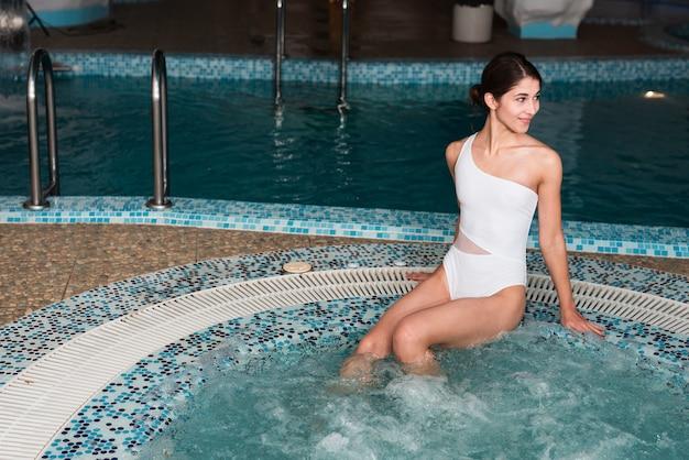 Tiro médio garota feliz posando na banheira de hidromassagem