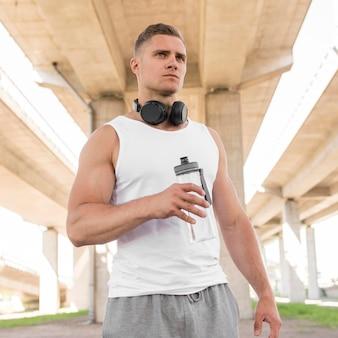 Tiro médio homem atlético, olhando para longe