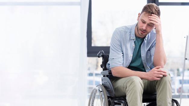 Tiro médio homem cansado em cadeira de rodas