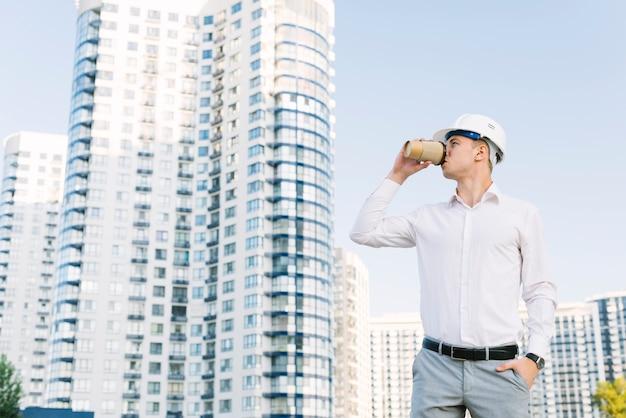 Tiro médio, homem, com, capacete, café bebendo