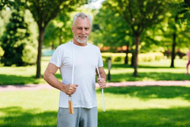 Tiro médio, homem, com, pular corda, ao ar livre