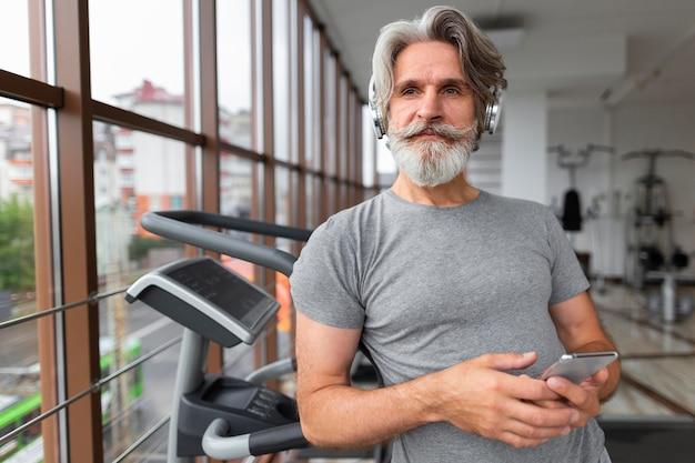 Tiro médio homem com telefone no ginásio