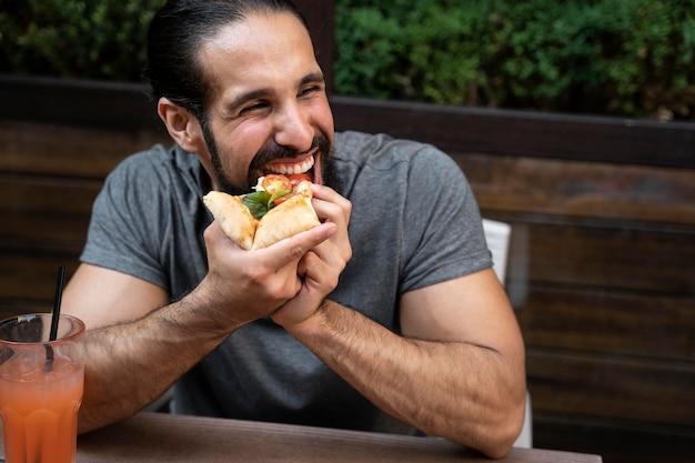 Tiro médio homem comendo pizza