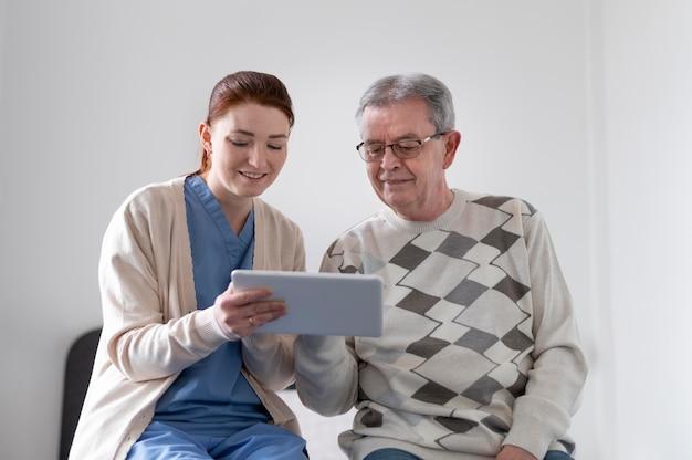 Tiro médio homem e mulher com tablet