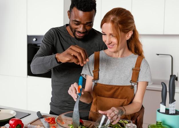 Tiro médio homem e mulher cozinhando