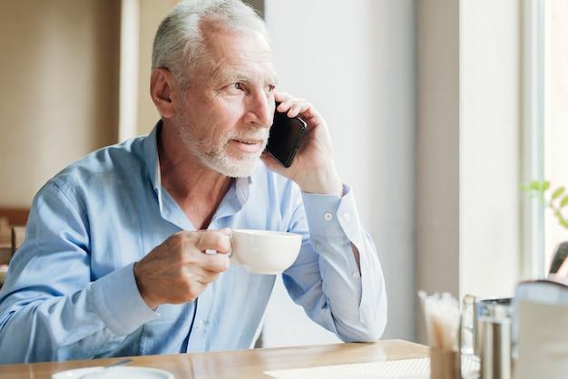 Tiro médio, homem fala, telefone, com, chá