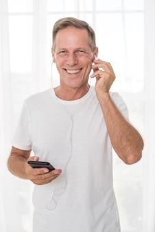 Tiro médio homem feliz com smartphone e fones de ouvido