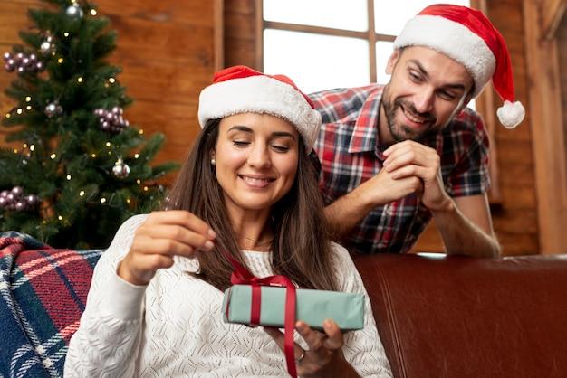 Tiro médio homem feliz, oferecendo um presente de sua esposa