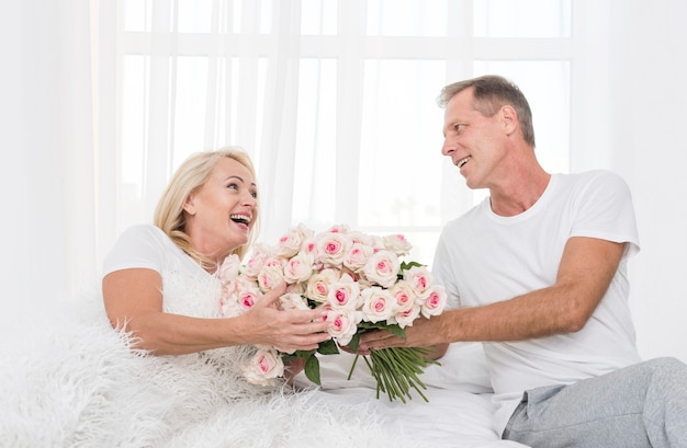 Tiro médio homem mulher surpreendente com buquê de flores