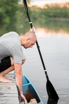Tiro médio homem segurando a raquete