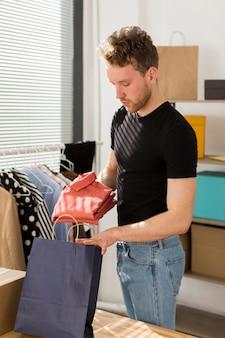 Tiro médio homem segurando o saco de papel
