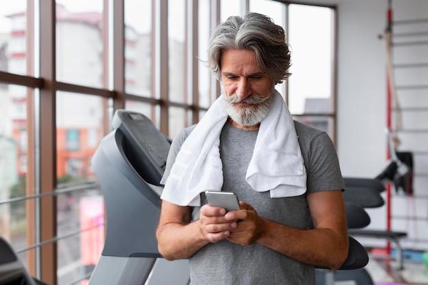 Tiro médio homem segurando smartphone