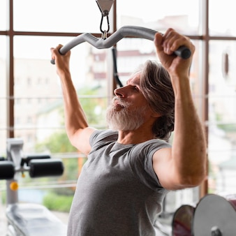 Tiro médio homem trabalhando no ginásio