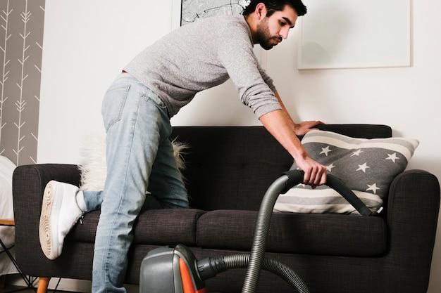 Tiro médio, homem, vacuuming, sofá