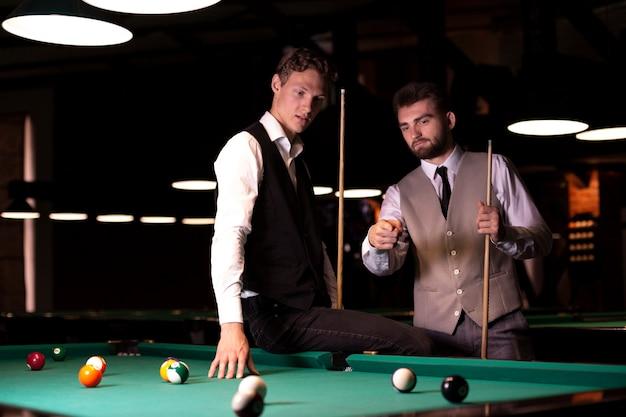 Tiro médio homens com coletes perto da mesa de bilhar