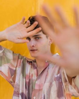 Tiro médio jovem rapaz posando com fundo amarelo