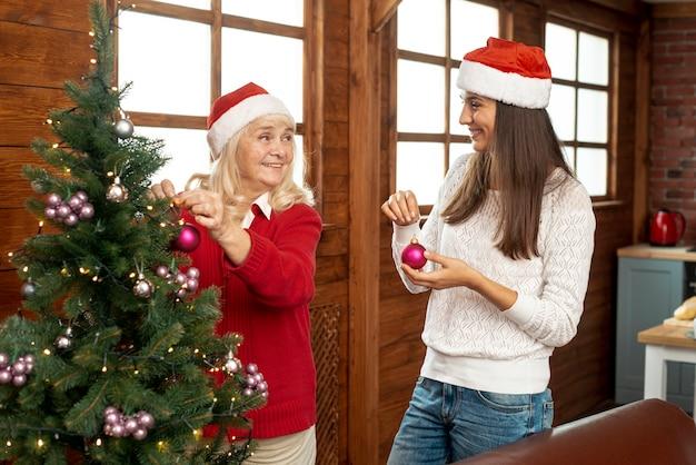 Tiro médio mãe e filha decorando a árvore de natal