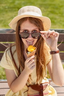 Tiro médio, menina, comer sorvete
